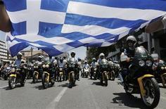 Manifestation des policiers municipaux grecs à Athènes contre la réforme du secteur public. Les ministres des Finances de la zone euro se sont entendus lundi sur le versement, par étapes, d'une tranche d'aide à la Grèce, dont 4,0 milliards d'euros qui seront versés avant la fin du mois. /Photo prise le 8 juillet 2013/REUTERS/John Kolesidis