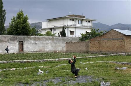 A boy plays with a tennis ball in front of Osama bin Laden's compound in Abbottabad in this May 5, 2011 file picture. REUTERS/Akhtar Soomro/Files