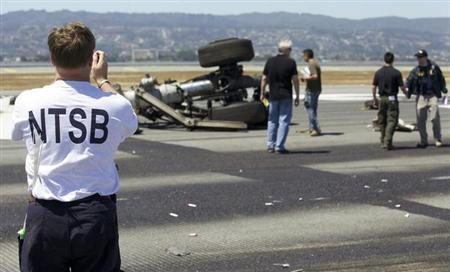 U.S. National Transportation Safety Board (NTSB) investigators attend to the scene of the Asiana Airlines Flight 214 crash site at San Francisco International Airport in San Francisco, California in this handout photo released on July 7, 2013. REUTERS/NTSB/Handout via Reuters