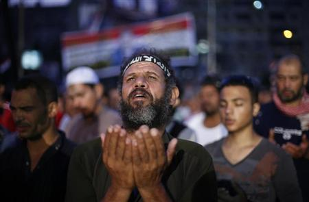 A supporter of deposed Egyptian President Mohamed Mursi attends night prayers during a protest outside the Rabaa Adawiya mosque in Cairo July 8, 2013. REUTERS/Suhaib Salem