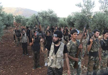 Free Syrian Army fighters, holding their weapons, stand during military training north of Idlib July 7, 2013. Picture taken July 7, 2013. REUTERS/Abdalghne Karoof