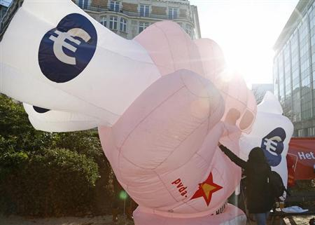 A protester pushes an inflatable balloon in the form of a clenched fist holding euro notes during a march against austerity measures in Brussels November 14, 2012. REUTERS/Francois Lenoir/Files