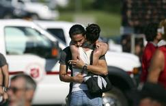 A man console his friend at the Polyvanlente Montignac, the school sheltering the people who were forced to leave their houses after the explosion, in Lac Megantic, July 8, 2013. REUTERS/Mathieu Belanger