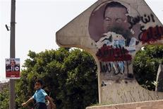 """An Egyptian boy walks near a defaced picture of former Egyptian President Hosni Mubarak with Arabic words reading, """"Corrupt and deposed"""" and a poster of presidential candidate and former leader of the Muslim Brotherhood Abdel Moneim Abol Fotouh (L) in Cairo May 24, 2012. REUTERS/Amr Abdallah Dalsh"""