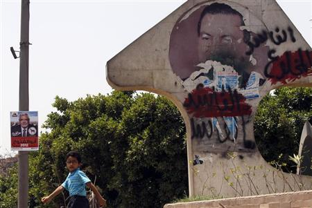 An Egyptian boy walks near a defaced picture of former Egyptian President Hosni Mubarak with Arabic words reading, ''Corrupt and deposed'' and a poster of presidential candidate and former leader of the Muslim Brotherhood Abdel Moneim Abol Fotouh (L) in Cairo May 24, 2012. REUTERS/Amr Abdallah Dalsh
