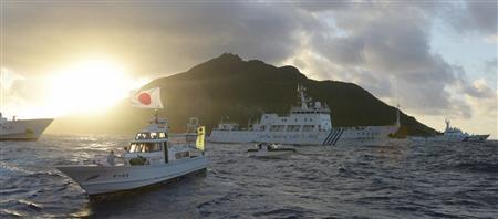 Chinese marine surveillance ship Haijian No. 51 (C) sails near Japan Coast Guard vessels (R and L) and a Japanese fishing boat (front 2nd L) as Uotsuri island, one of the disputed islands, called Senkaku in Japan and Diaoyu in China, is background, in the East China Sea in this photo taken by Kyodo July 1, 2013. REUTERS/Kyodo