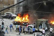 """Участники движений гражданской обороны и обычные жители южных окраин Бейрута на месте взрыва автомобиля 9 июля 2013 года. Несколько человек стали жертвами подрыва автомобиля в районе Бейрута, контролируемом шиитским движением """"Хезболла"""", сообщил корреспондент Рейтер, находящийся на месте происшествия. REUTERS/Issam Kobeisy"""
