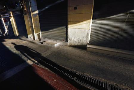 A man casts his shadow as he walks through a deserted Athens shopping area , October 18, 2012. REUTERS/Yannis Behrakis (GREECE - Tags: BUSINESS EMPLOYMENT) - RTR399SL