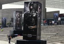 "Posters of the film ""The Dark Knight Rises"" are displayed outside as people wait for the midnight premiere of the final instalment of Christopher Nolan's Batman trilogy at the National Auditorium in Mexico City July 23, 2012. REUTERS/Henry Romero"
