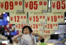 Funcionário arruma roupas sob cartazes com preços em supermercado de Hefei, na província de Anhui, China. A inflação anual ao consumidor da China acelerou mais do que o esperado em junho, mas os preços ao produtor registram deflação pelo 16º mês consecutivo, ressaltando o dilema do banco central da China em relação aos riscos de longo prazo para a inflação enquanto a economia desacelera. 9/07/2013. REUTERS/Stringer
