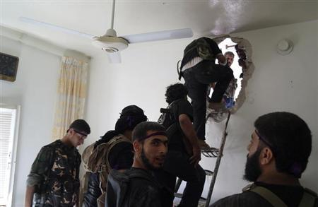 Free Syrian Army fighters climb up a ladder to walk through a hole in a wall during an offensive against forces loyal to Syria's President Bashar al-Assad, in Aleppo's Salaheddine neighborhood July 8, 2013. REUTERS/Ammar Abdullah
