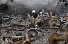 A police officer walks amongst axle gear in Lac Megantic, July 9, 2013. REUTERS/Mathieu Belanger