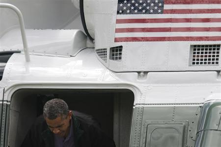 U.S. President Barack Obama ducks his head departing the Marine One helicopter as he returns from a weekend visit at Camp David to the White House in Washington, July 7, 2013. REUTERS/Jonathan Ernst