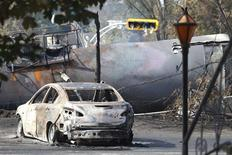 A burnt out vehicle sits near the wreckage of a train car after a train derailment in Lac-Megantic, Quebec, July 7, 2013. REUTERS/Christinne Muschi