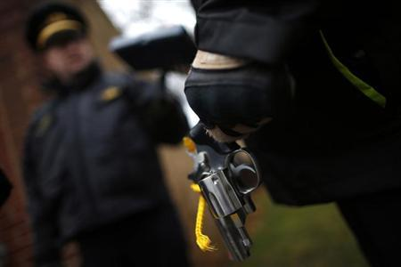 An Evanston police officer holds a firearm that was turned in as part of an amnesty-based gun buyback program in Evanston, Illinois December 15, 2012. REUTERS/Jim Young