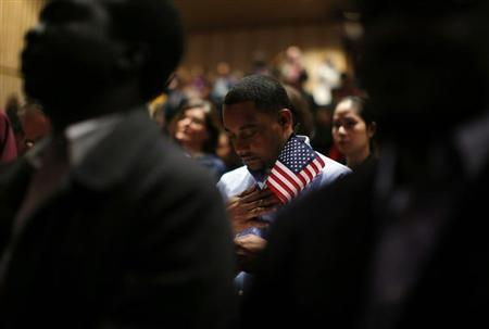 Immigrants stand for the invocation during a naturalization ceremony to become new U.S. citizens at Boston College in Chestnut Hill, Massachusetts March 21, 2013. REUTERS/Brian Snyder