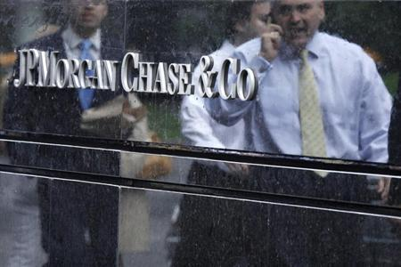 Commuters are reflected in stone as they walk past the JP Morgan headquarters in New York May 22, 2012. REUTERS/Eduardo Munoz