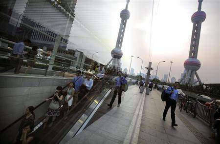 A man walks next to a subway entrance as the Oriental Pearl Tower is seen reflected on a window at the financial district of Pudong, in Shanghai July 8, 2013. REUTERS/Carlos Barria