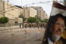 Изображение смещенного президента Египта на ограждении из колючей проволоки, за которым стоят солдаты республиканской гвардии, в Каире 9 июля 2013 года. Временные власти Египта, получившие $8 миллиардов в качестве финансовой помощи от стран Персидского залива, начали в среду формировать правительство - ровно через неделю после свержения военными президента-исламиста Мохамеда Мурси. REUTERS/Khaled Abdullah