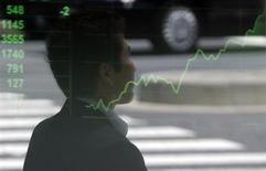 Прохожий отражается в экране с графиком динамики японского индекса Nikkei возле брокерской конторы в Токио 24 мая 2013 года. Азиатские фондовые рынки завершили торги среды разнонаправленно на фоне слабых внешнеторговых данных Китая. REUTERS/Issei Kato