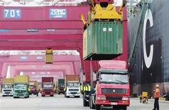 """Контейнеры переносят на грузовики в порту города Циндао 8 мая 2013 года. Китай предупредил в среду о """"мрачном"""" прогнозе для торговли, поскольку вторая мировая экономика удивила рынки, сообщив о сокращении экспорта и импорта при прогнозе их роста. REUTERS/China Daily"""