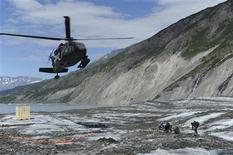 Members of a specialized investigative team from the Joint POW/MIA Accounting Command wait as a UH-60 Blackhawk helicopter comes in for a landing to transport them back to base after a day of assessing a historic aircraft crash site at Colony Glacier, Alaska, in this June 24, 2013 handout photo released to Reuters on July 8, 2013. REUTERS/U.S. Navy Mass Communications Specialist 3rd Class Clifford Bailey/Department of Defense/Handout via Reuters