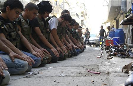 Free Syrian Army fighters pray along a street in Aleppo's Salaheddine neighbourhood July 9, 2013. REUTERS/Ammar Abdullah