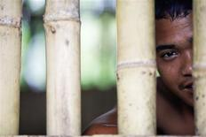 "La Aung looks out from inside a bamboo cell called the ""Special Prayer Room"", where he is locked in for his first week at the Youth for Christ Centre for heroin addicts, near Naung Chein in Myanmar's Kachin state July 5, 2013. REUTERS/Damir Sagolj"