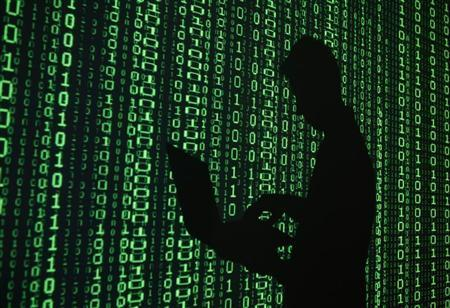 An illustration picture shows a projection of binary code around the shadow of a man holding a laptop computer in an office in Warsaw June 24, 2013. REUTERS/Kacper Pempel