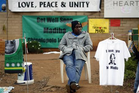 A street vendor sells t-shirts and fabric outside the hospital where ailing former President Nelson Mandela is being treated in Pretoria, July 10, 2013. REUTERS/Mike Hutchings