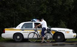 A cyclist speaks with a police officer in Lac Megantic, July 9, 2013. REUTERS/Mathieu Belanger