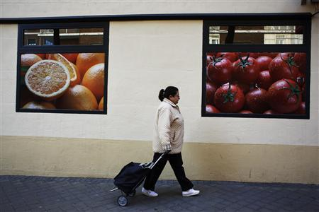 A woman pulls a shopping cart as she comes out of a supermarket in Madrid April 23, 2013. REUTERS/Susana Vera