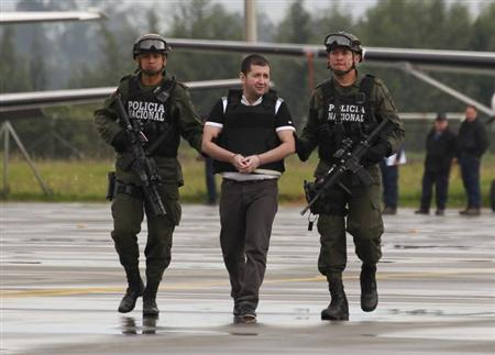 Police escort Colombian drug trafficker Daniel 'El Loco' Barrera (C) as he is brought before the media, before being extradited to the U.S., at an airport in an anti-narcotics base in Bogota July 9, 2013. REUTERS/John Vizcaino