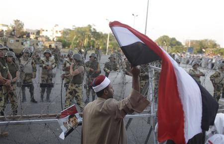 A supporter of ousted Egyptian President Mohamed Mursi waves an Egyptian flag in front of security personnel outside of the Republican Guard headquarters as Mursi supporters camp for the third day, in Cairo July 7, 2013. REUTERS/Asmaa Waguih