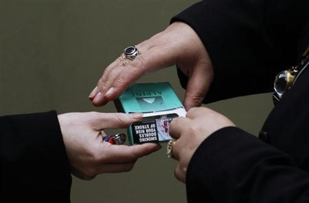 Women handle a cigarette pack in central Sydney October 12, 2011. REUTERS/Daniel Munoz