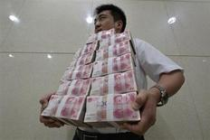An employee carries bundles of 100 yuan Chinese bank notes to store after counting at a bank in Taiyuan, Shanxi province July 4, 2013. REUTERS/Jon Woo