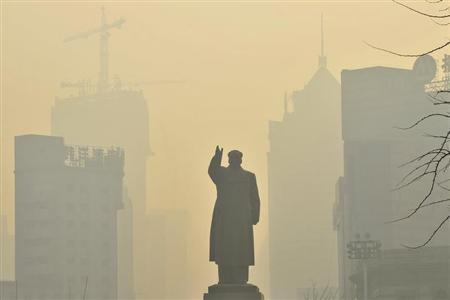 A statue of China's late Chairman Mao Zedong is seen in front of buildings during a hazy day in Shenyang, Liaoning province, May 7, 2013. REUTERS/Stringer