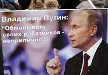 """Участница пикета в Красноярске держат плакат с изображением Владимира Путина 10 ноября 2010 года. Москва - застрельщик антипутинских выступлений - охладела к демократии и не так озабочена доходами, как """"дальнее Замкадье"""". Провинция же готова отозваться на экономическую стагнацию жёсткими протестами, против которых Кремль не рискнёт действовать как на Болотной, считают аналитики, предсказавшие крупнейшие за 13-летнее правление Путина массовые акции. REUTERS/Ilya Naymushin"""