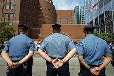 """Полицейские стоят у здания суда в Бостоне, в котором слушается дело Джохара Царнаева, 10 июля 2013 года. Одетый в оранжевый тюремный комбинезон и с гипсом на левой руке, обвиняемый по делу о взрывах во время проведения Бостонского марафона Джохар Царнаев заявил в суде, что """"не виновен"""" в преступлении, которое грозит ему смертной казнью. REUTERS/Brian Snyder"""