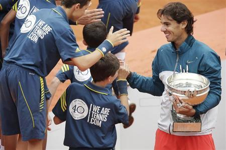 Rafael Nadal of Spain holds his trophy as he shakes hands with ball boys after defeating compatriot David Ferrer in their men's singles final match to win the French Open tennis tournament at the Roland Garros stadium in Paris June 9, 2013. REUTERS/Philippe Wojazer/Files