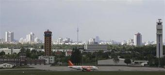 An aircraft operated by easyJet sits on tarmac with the skyline of German capital of Berlin in the background at Schoenefeld airport, May 17, 2012. REUTERS/Tobias Schwarz