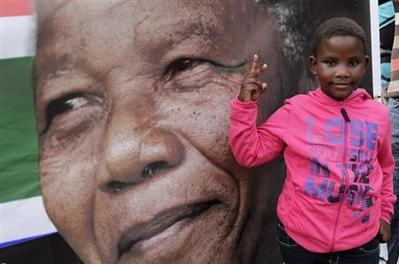 A girl gestures near a picture of ailing former South African President Nelson Mandela, outside the Medi-Clinic Heart Hospital where he is being treated in Pretoria July 6, 2013. REUTERS/Thomas Mukoya/Files
