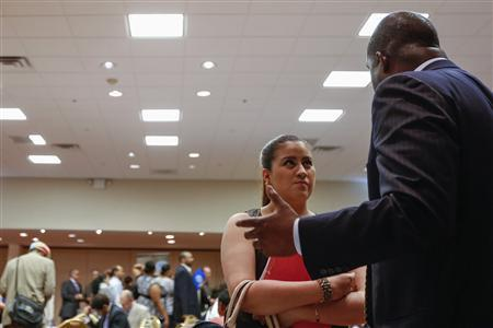 A woman stands with her paperwork as she speaks with a recruiter while attending a job fair in New York in this file photo taken June 11, 2013. REUTERS/Lucas Jackson/Files