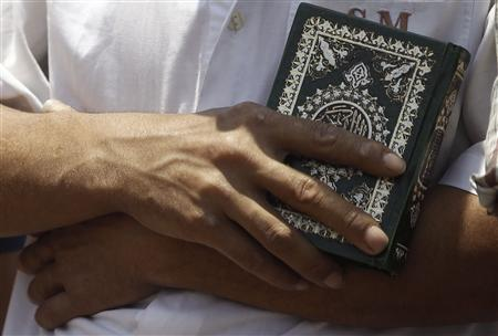 A member of the Muslim Brotherhood and supporter of deposed Egyptian President Mohamed Mursi holds the Koran as he performs afternoon prayers at the Rabaa Adawiya square, where they are camping at, in Cairo July 11, 2013. REUTERS/Amr Abdallah Dalsh