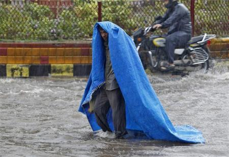 A man uses a plastic sheet to protect himself from a heavy rain shower in Ahmedabad July 4, 2013. REUTERS/Amit Dave