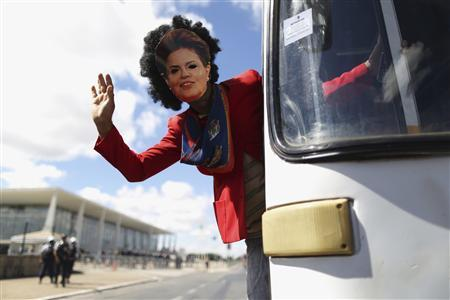 A man wearing a mask depicting Brazil's President Dilma Rousseff waves from a bus during the National Day of Struggle, a march by unionists, at the Planalto Palace in Brasilia July 11, 2013. REUTERS/Ueslei Marcelino