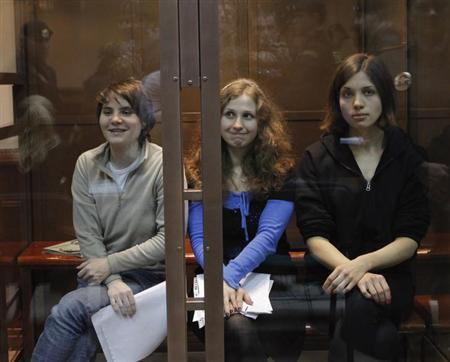Members of the female punk band ''Pussy Riot'' (L-R) Yekaterina Samutsevich, Maria Alyokhina and Nadezhda Tolokonnikova sit in a glass-walled cage before a court hearing in Moscow October 10, 2012 file photo. REUTERS/Maxim Shemetov