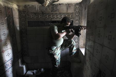 A Free Syrian Army fighter aims his weapon as he takes position inside a house in the city of Aleppo July 11, 2013. REUTERS/Muzaffar Salman