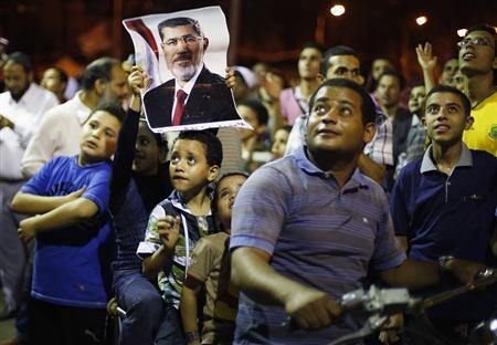 A supporter of the deposed Egyptian President Mohamed Mursi and his sons sit on a motorbike as they listen to a speech during a sit-in protest in Cairo July 11, 2013. REUTERS/Suhaib Salem