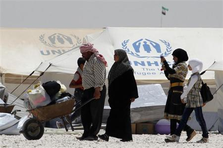 A newly arrived Syrian refugee receives aid and rations, at Al-Zaatri refugee camp in the Jordanian city of Mafraq, near the border with Syria, on World Refugee Day, June 20, 2013. REUTERS/Muhammad Hamed